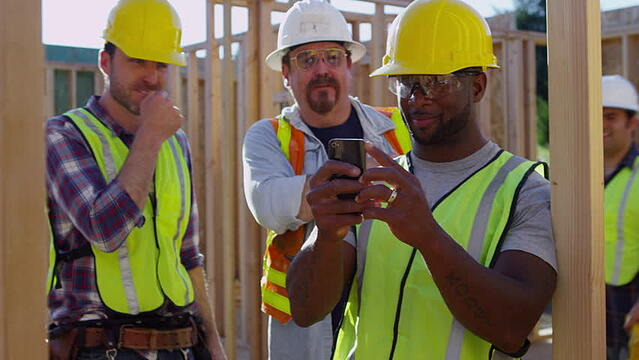 constructin workers using mobile to take jobsite photos